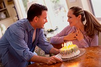 Mid adult couple celebrating a birthday with a cake