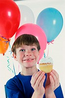 Boy holding a cupcake with balloons behind him