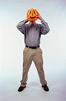Man holding a carved Halloween pumpkin in front of his face