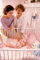 Two women looking at a baby girl in a crib