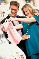 Pregnant woman with her husband shopping for baby clothes