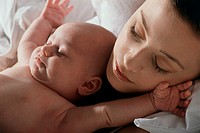 Close-up of a mother and her baby boy sleeping