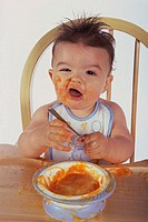 Portrait of a baby boy sitting on a chair eating