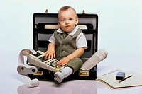 Portrait of a baby boy sitting in an open briefcase holding an adding machine