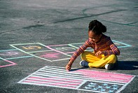Girl drawing the American flag on the ground with chalk