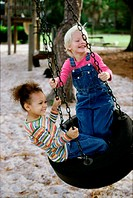 Two girls playing on a swing