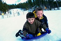 Two boys riding on a sled