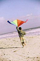 Rear view of a boy flying a kite on the beach
