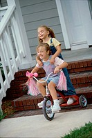 Two girls playing on a tricycle