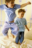 Close-up of two boys playing on a bed