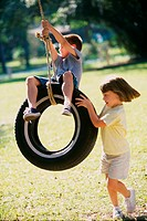 Girl pushing a boy on a tire swing