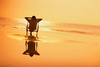 Silhouette of a young woman sitting in a chair on the beach