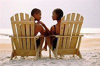 Rear view of a young couple sitting in chairs on the beach