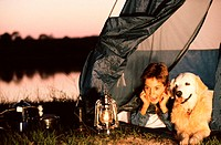 Boy lying in a tent with his dog