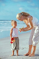 Mother showing her daughter a starfish on the beach