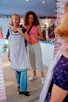Two young women trying on clothes in a clothing store