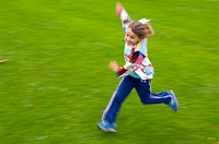 Girl child dressed in patchwork jacket running crazy on grass