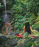 Polynesian woman, in front of lush waterfall.