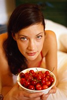 Young woman holding bowl of fresh cherries