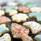 Colourfully decorated Christmas biscuits on cake rack