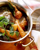 Beef broth with soup vegetables and parsley in copper pan