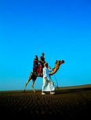 Western tourists riding a camel in the desert, UAE