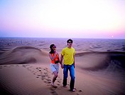 Western couple walking in the desert near Hatta, United Arab Emirates