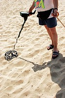 Person with metal detector on the beach
