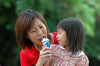 Mother sharing ice-cream with daughter, Malaysia