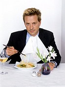 businessman with napkin eating noodles with chopsticks