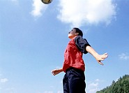 teenage girl in football dress doing a header