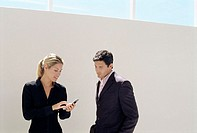 Businesswoman showing businessman her phone