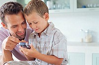 Father showing son how to use mobile phone
