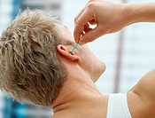 Man putting cotton bud in his ear