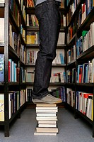 Young person standing on books in library