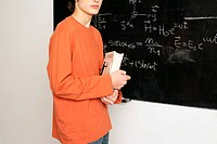 Young man with book in front of blackboard