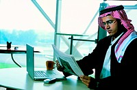 Saudi businessman reading newspaper in the office