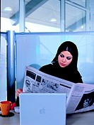 Emirati businesswoman reading newspaper in the office