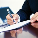 Businessman signing document at desk, close-up of hands