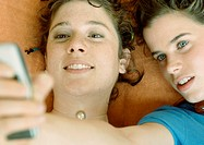 Young women looking at cell phone, close-up