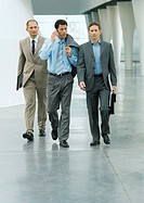 Three businessmen walking through lobby, one using cell phone (thumbnail)