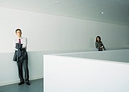 Businessman and businesswoman standing apart in office building
