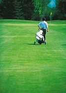 Golfer pulling golf bag on green
