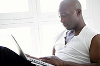 A black male in casual dress using a laptop