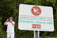 Male birder, binoculars. Coastal Birding Trail sign, Dauphin Island. Alabama. USA.