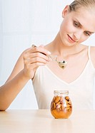 Woman holding spoon over jar of almonds and honey
