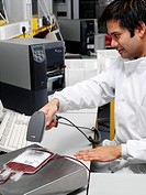Donor blood processing. Researcher scanning the barcode on a bag of donor blood. All blood products are given a barcode so they can be kept track of t...