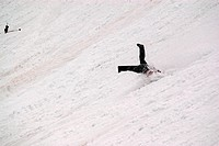Legs of a skier sticking out of snow