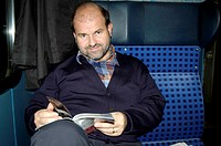 A middle-aged man readin a magazine on a train