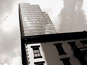 Two very different type of typical New York City buildings: one, a new modern type skyscraper, the other an older tenement building.  This image was t...